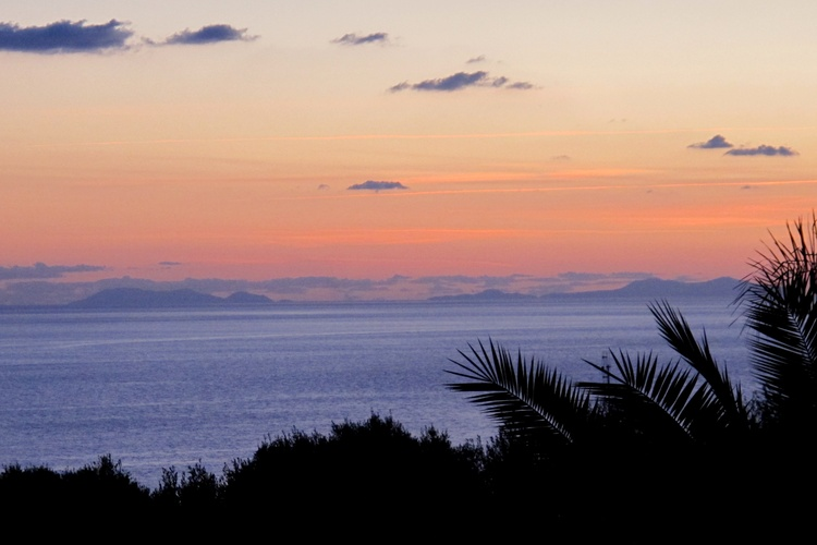 Balcony sunset view of the Aeolian Islands on the horizon