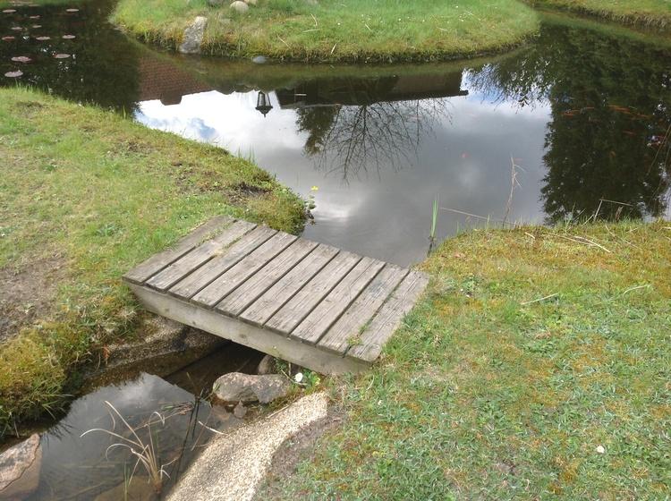 Brücke über künstlichen Bachlauf am Gartenteich